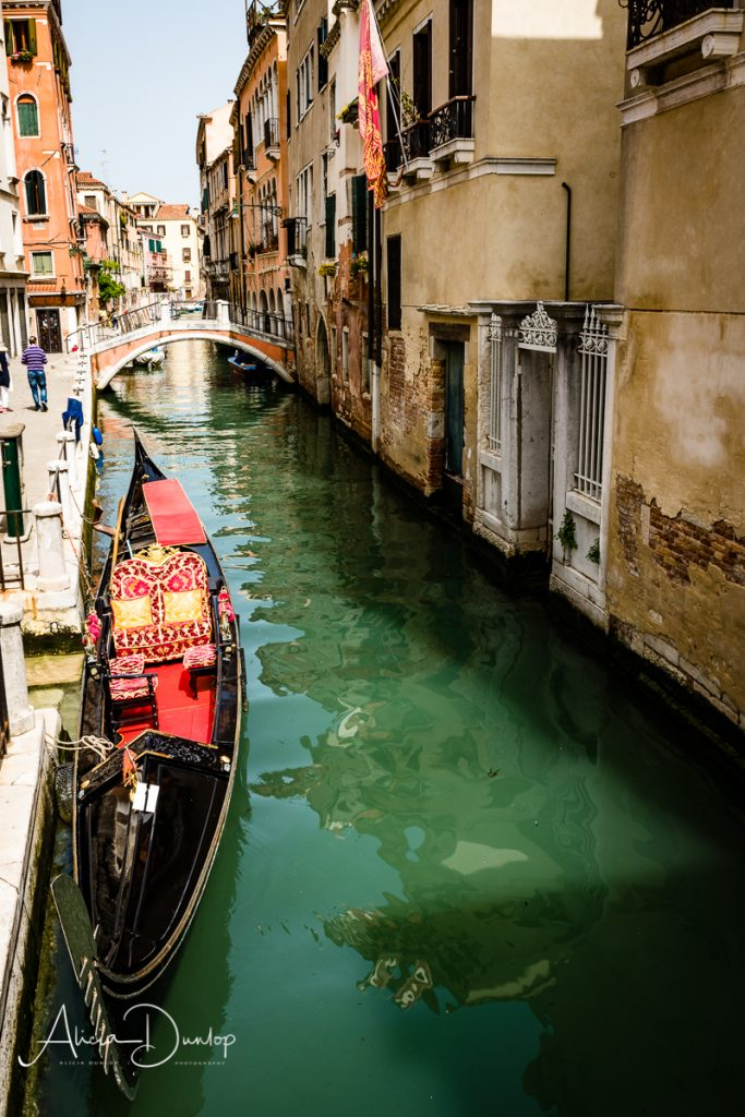 A gondola in a quiet narrow canal in Venice