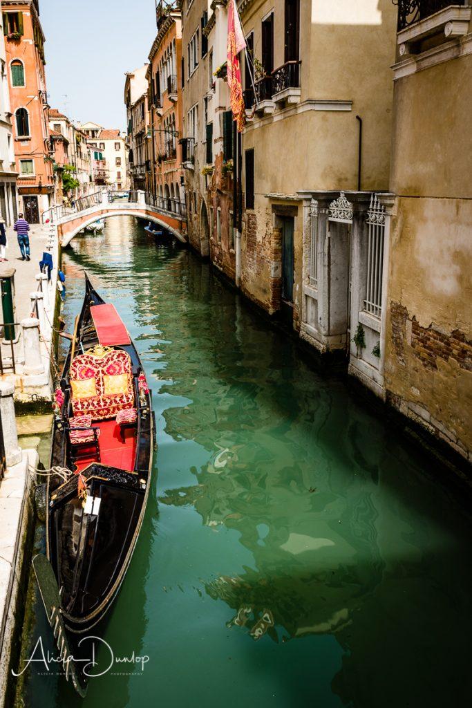 A gondola in a quiet narrow canal in Venice